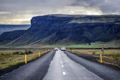 Ingen väg 1 i Island, asfalt, berg och körningsbilar i th Royaltyfri Fotografi