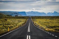 Ingen väg 1 i Island, asfalt, berg och körningsbilar i th Arkivbild