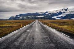 Ingen väg 1 i Island, asfalt och berg med en glaciär i t Royaltyfri Foto
