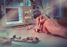 Ingeneer or tech tests electronic equipment. Senior male engineer or tech tests electronic equipment in hardware service centre. This picture is toned Stock Image