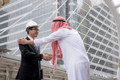 Ingeniería asiática de sacudida de las manos del hombre de negocios árabe sobre una negociación del trato al éxito foto de archivo