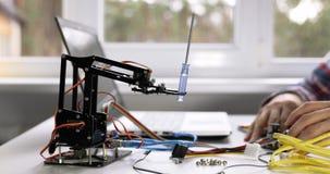 Ingeniería de la robótica - brazo del robot de programación del técnico en el ordenador almacen de metraje de vídeo