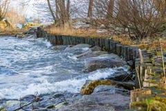 Ingeniería natural - bioingeniería del suelo Protección de orilla contra la erosión de agua con los troncos de madera Imagen de archivo