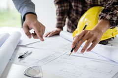 Ingeniería o arquitecto de construcción discutir un modelo mientras que comprueba la información sobre el dibujo y bosqueja la re fotos de archivo libres de regalías