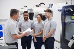 Ingeniería Team Meeting On Factory Floor del taller ocupado fotografía de archivo