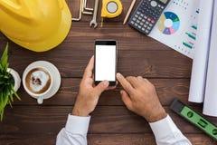 Ingeniería usando el teléfono en su opinión superior del espacio de trabajo imagen de archivo libre de regalías