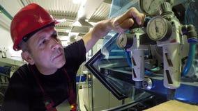 Ingeniero Adjusts el regulador de presión en la máquina
