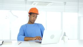 Ingeniero afroamericano que trabaja en el ordenador portátil en oficina metrajes