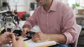 Ingeniero alegre que discute la pista de oruga robótica con su colega