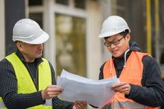 Ingeniero asiático del aprendiz en el trabajo sobre emplazamiento de la obra con el alto directivo imagen de archivo