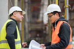 Ingeniero asiático del aprendiz en el trabajo sobre emplazamiento de la obra con el alto directivo fotos de archivo