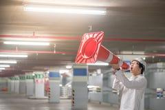 Ingeniero asiático joven que grita sin embargo el cono de la seguridad de tráfico en parki Fotografía de archivo