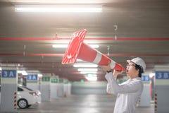 Ingeniero asiático joven que grita sin embargo el cono de la seguridad de tráfico en parki Fotografía de archivo libre de regalías