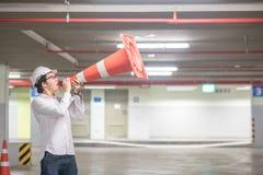 Ingeniero asiático joven que grita sin embargo el cono de la seguridad de tráfico en parki Imagen de archivo