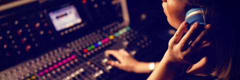 Ingeniero audio de sexo femenino que escucha los auriculares Fotos de archivo