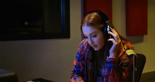 Ingeniero audio de sexo femenino que usa el mezclador de sonidos almacen de metraje de vídeo
