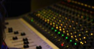 Ingeniero audio de sexo femenino que usa el mezclador de sonidos metrajes