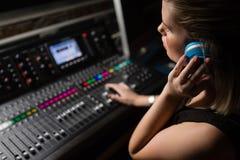 Ingeniero audio de sexo femenino que usa el mezclador de sonidos Fotografía de archivo libre de regalías