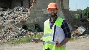 Ingeniero barbudo del constructor con una tableta y los dibujos que sonr?e y que mira la c?mara almacen de video
