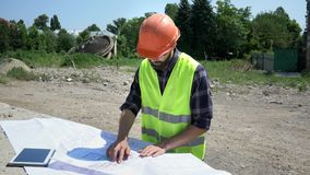 Ingeniero barbudo del constructor en casco anaranjado que analiza el dibujo Preparaci?n para la construcci?n almacen de video