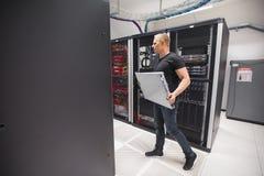 Ingeniero Carrying Blade Server de las TIC mientras que camina en Datacenter Imagenes de archivo