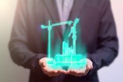 Ingeniero civil que celebra una construcción de edificios de la grúa del holograma imagen de archivo libre de regalías