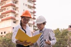 Ingeniero civil y arquitecto sonrientes que trabajan en una construcción s Foto de archivo