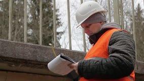 Ingeniero con cinta métrica y documentación cerca del puente metrajes