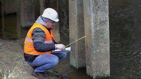Ingeniero con cinta métrica y documentación debajo del puente almacen de metraje de vídeo