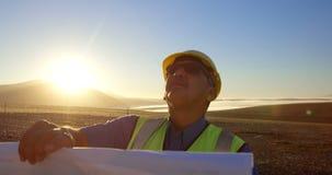 Ingeniero con el modelo que se coloca en el parque eólico 4k almacen de metraje de vídeo