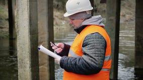 Ingeniero con el teléfono celular y documentación debajo del puente almacen de metraje de vídeo
