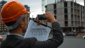 Ingeniero con el teléfono elegante que toma imágenes de la construcción almacen de metraje de vídeo