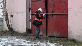 Ingeniero con la tableta y documentación cerca del edificio almacen de metraje de vídeo
