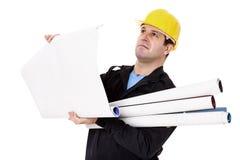Ingeniero con los rollos de los estudios del papel a disposición Fotografía de archivo libre de regalías