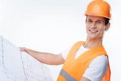 Ingeniero confiado elegante que sostiene su proyecto Imagen de archivo