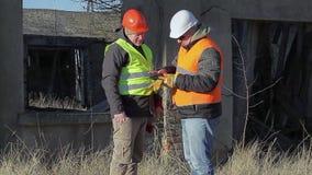 Ingeniero de construcción con el edificio destruido cercano de la tableta almacen de video