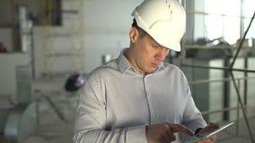 Ingeniero de construcción con la tableta Imágenes del emplazamiento de la obra A cámara lenta almacen de video
