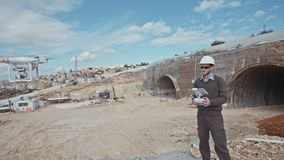 Ingeniero de construcción que usa un abejón para la fotografía aérea en un emplazamiento de la obra almacen de metraje de vídeo