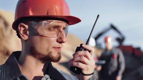 Ingeniero de construcci?n de sexo masculino experto en la informaci?n del uniforme usando el Walkietalkie durante el primer de tr almacen de metraje de vídeo
