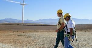 Ingeniero de dos varones que camina en el parque eólico 4k almacen de metraje de vídeo
