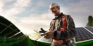 Ingeniero de energía solar usando la tableta para la sonrisa de la central eléctrica del control imágenes de archivo libres de regalías