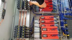 Ingeniero de la automatización que trabaja en los cables para el sistema de control almacen de video