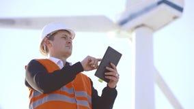 Ingeniero de la energía del molino de viento a trabajar con la tableta en la puesta del sol ambiental almacen de video