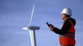 Ingeniero de la energía del molino de viento a trabajar con la tableta en la puesta del sol ambiental metrajes
