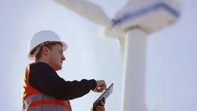 Ingeniero de la energía del molino de viento a trabajar con la tableta en la puesta del sol ambiental almacen de metraje de vídeo
