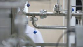 Ingeniero de la fábrica que examina la tubería del laboratorio durante trabajo almacen de metraje de vídeo