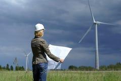 Ingeniero de la mujer con la turbina de viento blanca del sombrero de seguridad Imágenes de archivo libres de regalías