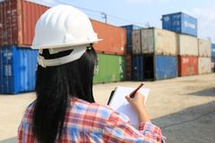 Ingeniero de la mujer joven que comprueba el producto de las importaciones/exportaciones en el fondo delantero del envase, transp imagen de archivo
