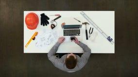 Ingeniero de la oficina que usa el teléfono móvil que se sienta en su escritorio almacen de video