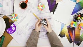 Ingeniero de la visión superior que trabaja en un bosquejo del diseño del coche y que juega con el cubo inusual de Rubiks metrajes